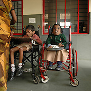 Rathna Priya (8) in her wheel chair during lunch time at the APD School in Bangalore. She suffers from Rickets and has a 'pigeon chest'. Although she can now read and scribble, and somehow manages to eat on her own, she is completely dependant on others.