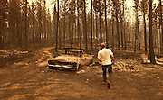 DIGITAL IMAGE. NO SHARPENING OR NOISE REDUCTION APPLIED.   Bathed in light colored by thick smoke from the largest wildfires in the nation (double check this), Mike Jennings checks the remains of one of his newly restored cars on his property in Sula, Montana. Jennings lost trees, a mobile home and  all his shop and other out buildings, but was fortunate enough to still have his main house.