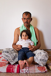 © Licensed to London News Pictures. Hamdaniyah, Iraq. 25/07/2014. Hamdaniyah, Iraq.Christian refugee Ra'id Samir Kamal (45), formerly a driver in Mosul, holds his five year old daughter, Rania, at the home they now share with 15 other members of their extended family in Hamdaniyah, Iraq. Samir left Mosul on Friday the 18th of July when Islamic State fighters issued an ultimatum to the city's Christian community. When the family left they were forced to pay a tax for their car, their son (19) was threatened at knifepoint to ensure they handed over all of their possessions including family photographs.<br /> <br /> Having taken over Mosul Iraq's second largest city in June 2014, fighter of the Islamic State (formerly known as ISIS) have systematically expelled the cities Christian population. Despite having been present in the city for more than 1600 years, Christians in the city were given just days to either convert to Islam, pay a tax for being Christian or leave; many of those that left were also robbed at gunpoint as they passed through Islamic State checkpoints.. Photo credit : Matt Cetti-Roberts/LNP
