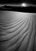 Black and white of Death Valley sand dunes at sunset and dramatic shadows and ridges in the sand.