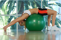 Woman Bending Backwards Over Exercise Ball