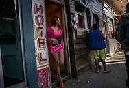 "Paradita (""Standing Girl"") sex worker emerges from a hotel in the Coahila District of Zona Norte, the red light district just a three blocks from the Us/Mexico border.   Tijuana, Mexico  Many of the sex workers in Zona Norte tried but failed to cross the border and remain stranded in Tijuana without work."