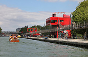 Galerie de l'Ourcq, a walkway in the Parc de la Villette, alongside the Canal de l'Ourcq, with 2 of the 26 red metal follies designed by Bernard Tschumi which are in the park, in the 19th arrondissement of Paris, France. On the right is the Folie de L'Aventure and in the distance, the Petite Folie. The Canal de l'Ourcq is a 108.1km waterway begun in 1802 between Port-aux-Perches and the Canal Saint-Martin via the Bassin de la Villette or La Villette Basin. Picture by Manuel Cohen