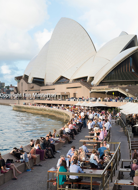 Evening view of Sydney Opera House with crowds of people drinking at many outdoor bars in Sydney Australia
