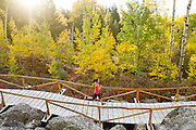Trail runner crossing a bridge. Jackson Hole, Wyoming