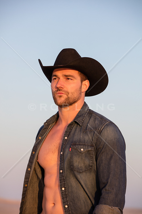 sexy rugged cowboy with an open shirt outdoors