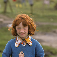 Ireland, County Galway, Young girl holds doll while playing on farm in Connemara