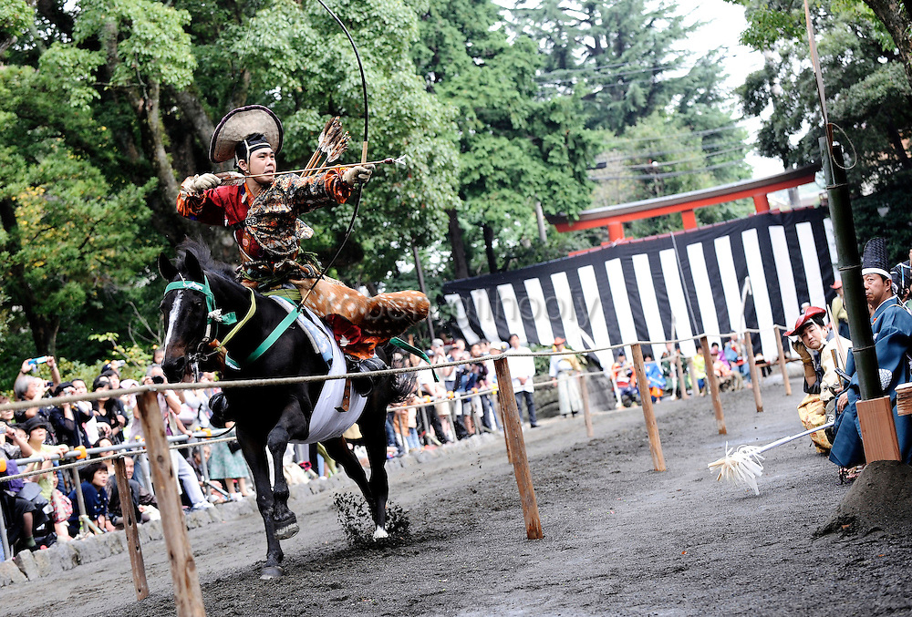 A horseback archer dressed in a traditional hunting garb aims an arrow at a target as his horse gallops along a 255-meter course at full pace during the Yabusame Shinji, a Japanese ritual, at Tsurugaoka Hachimangu shrine in Kamakura, near Tokyo. The ritual, which dates back to the 12th century and is aimed at appeasing the numerous gods that guard Japan, was initiated by Kamakura shogun Minamoto no Yoritomo  in an attempt to improve his samurai warrior's appalling archery skills.