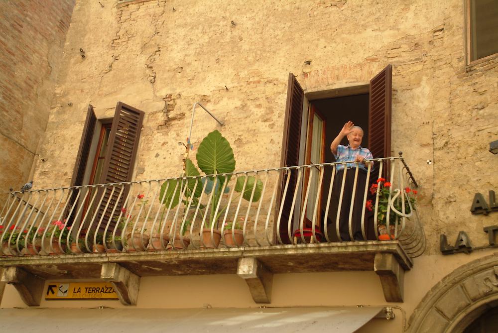 Old man waving from balcony in Cortona, Italy