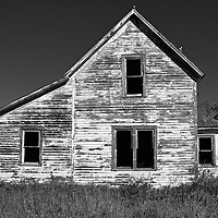 Abandoned timber home in rural location under summer skies in Eddy County USA