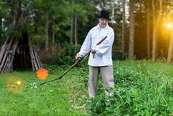 Farmer using scythe to mow grass traditionally in Estonia. Hut, meadow, sun flare. Haymaking.