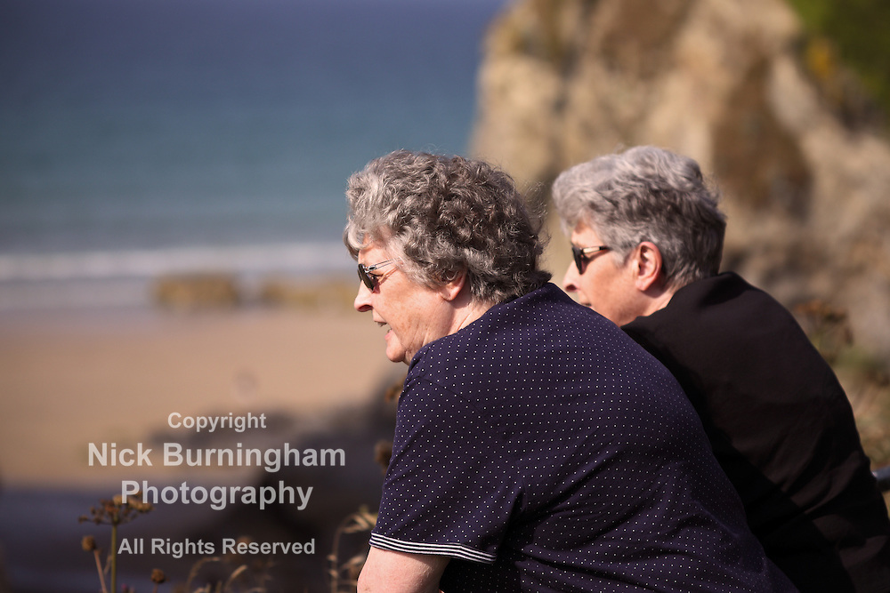 Twin elderly sisters look over a fence to the ocean beyond - EXCLUSIVELY AVAILABLE HERE