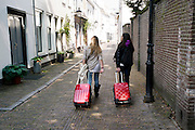 Twee vrouwen lopen met koffers achter zich aan door de binnenstad van Utrecht.<br /> <br /> Two women are walking with trolleys at downtown Utrecht.