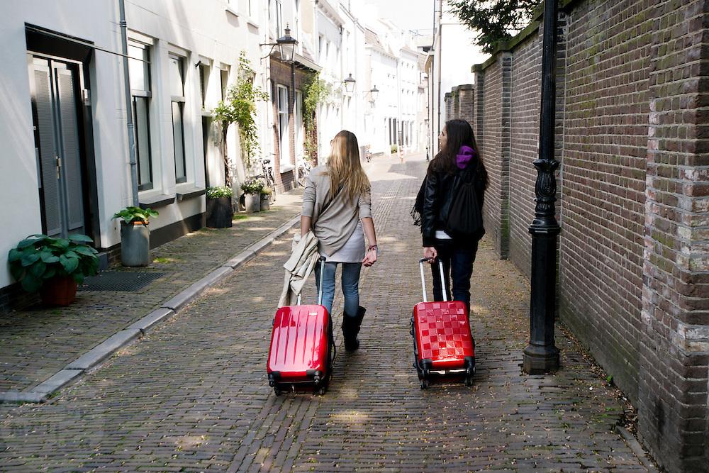Twee vrouwen lopen met koffers achter zich aan door de binnenstad van Utrecht.<br /> <br /> Two women are walking with trolleys at downtown Utrecht.