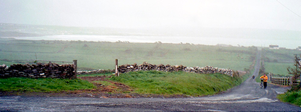 Far distant view of the Cliffs of Mohr as a cyclist comes up the hill on the west coast of Ireland in May 2002. (Christina Paolucci, photographer)