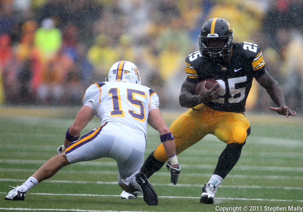 September 3, 2011: Iowa Hawkeyes running back Mika'il McCall (25) tries to avoid Tennessee Tech Golden Eagles cornerback Caleb Mitchell (15) during the first half of the game between the Tennessee Tech Golden Eagles and the Iowa Hawkeyes at Kinnick Stadium in Iowa City, Iowa on Saturday, September 3, 2011. Iowa defeated Tennessee Tech 34-7 in a game stopped at one point due to lightning and rain.