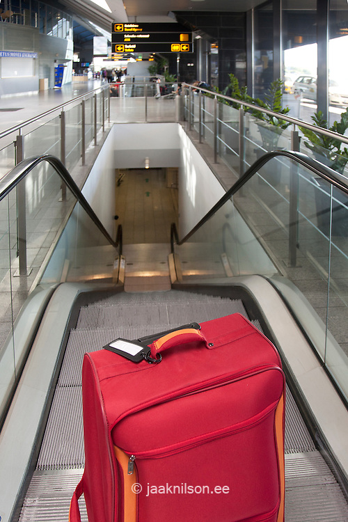 luggage at the top of escalator
