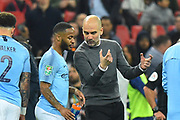 Manchester City manager Pep Guardiola talking to Raheem Sterling (7) of Manchester City at extra time half time during the Carabao Cup Final match between Chelsea and Manchester City at Wembley Stadium, London, England on 24 February 2019.