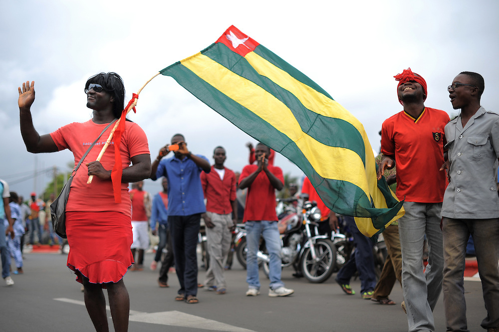 LOME, TOGO - 12-09-20   - Patrice Samey, dressed as a woman, waves to police officers as he joins the women's protest.  Approximately 300 women dressed in red marched through the Togolese capital city of Lomé on Thursday, September 20 as part of a protest organized by the opposition coalitions Lets Save Togo (Collectif Sauvons le Togo, CST) and Coalition ARC-EN-CIEL.  Several thousand men and youths joined the women in the peaceful march, which ended at an opposition rally point.  Photo by Daniel Hayduk/ AFP
