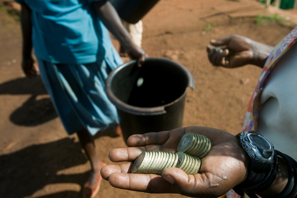 Africa, Kenya, Ruira, Coffee pickers collect payment of 40 Kenyan Shillings for each bucket of coffee cherries at collection site at Oakland Estates coffee plantation