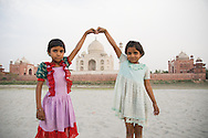 Two village girls pose like tourists with the Taj Mahal, India