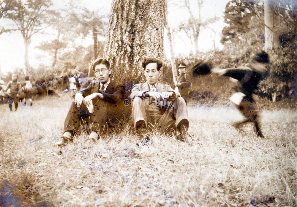 two men sitting among little children playing outdoors Japan ca 1940s