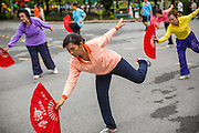 06 OCTOBER 2012 - BANGKOK, THAILAND:  Women do Tai Chi exercises with fans in Lumphini Park in Bangkok. The Thai government promotes exercise classes as a way staying healthy. Lumphini Park is 142 acre (57.6-hectare) park in Bangkok, Thailand. This park offers rare open public space, trees and playgrounds in the congested Thai capital. It contains an artificial lake where visitors can rent boats. Exercise classes and exercise clubs meet in the park for early morning workouts and paths around the park totalling approximately 1.55 miles (2.5 km) in length are a popular area for joggers. Cycling is only permitted during the day between the times of 5am to 3pm. Smoking is banned throughout smoking ban the park. The park was created in the 1920's and named after Lumbini, the birthplace of the Buddha in Nepal.   PHOTO BY JACK KURTZ