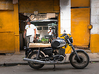 A man leaving a shop with a EMZ motorcycle out front in Havana Centro.