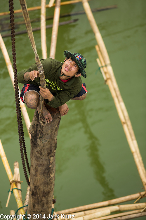 17 SEPTEMBER 2014 - SANGKHLA BURI, KANCHANABURI, THAILAND: A Thai soldier stands on a piling during repair work on the Mon Bridge. The 2800 foot long (850 meters) Saphan Mon (Mon Bridge) spans the Song Kalia River. It is reportedly second longest wooden bridge in the world. The bridge was severely damaged during heavy rainfall in July 2013 when its 230 foot middle section  (70 meters) collapsed during flooding. Officially known as Uttamanusorn Bridge, the bridge has been used by people in Sangkhla Buri (also known as Sangkhlaburi) for 20 years. The bridge was was conceived by Luang Pho Uttama, the late abbot of of Wat Wang Wiwekaram, and was built by hand by Mon refugees from Myanmar (then Burma). The wooden bridge is one of the leading tourist attractions in Kanchanaburi province. The loss of the bridge has hurt the economy of the Mon community opposite Sangkhla Buri. The repair has taken far longer than expected. Thai Prime Minister General Prayuth Chan-ocha ordered an engineer unit of the Royal Thai Army to help the local Mon population repair the bridge. Local people said they hope the bridge is repaired by the end November, which is when the tourist season starts.    PHOTO BY JACK KURTZ