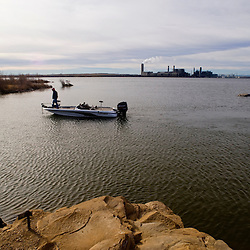 A fisherman puts his boat in at Morgan Lake as the Four Corners Power Plant operates in the background.