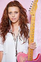 Portrait of stylish teenage girl holding guitar