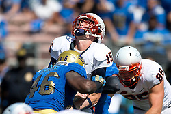 PASADENA, CA - SEPTEMBER 05:  Quarterback Matt Johns #15 of the Virginia Cavaliers is hit by linebacker Kene Orjioke #46 of the UCLA Bruins after throwing a pass during the third quarter at the Rose Bowl on September 5, 2015 in Pasadena, California. The UCLA Bruins defeated the Virginia Cavaliers 34-16. (Photo by Jason O. Watson/Getty Images) *** Local Caption *** Matt Johns; Kene Orjioke
