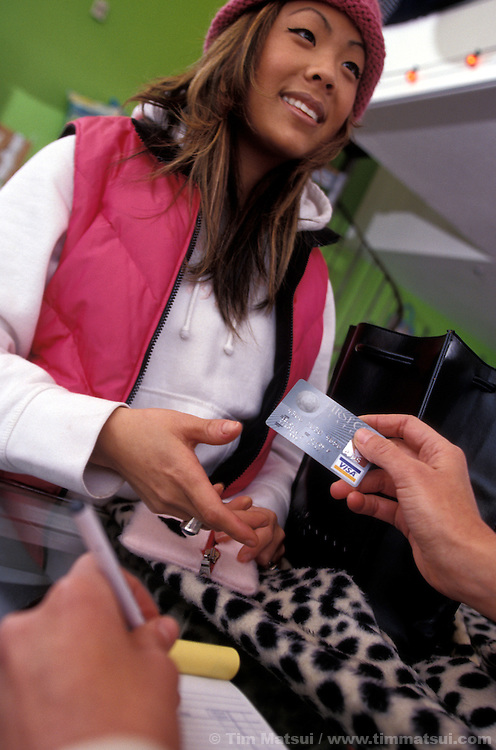 An asian woman in her early 20's buys clothing with a credit card in Seattle, Washington..