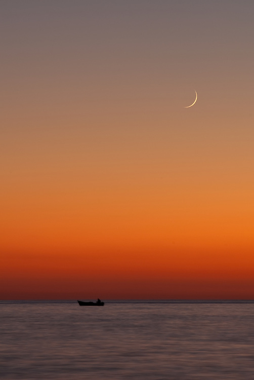 The moon appearas as the sunsets on a fisherman of Chora Sfakion, Crete.