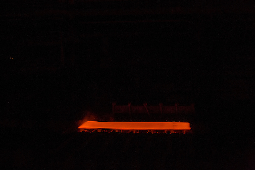 A glowing hot piece of steel rolls through the production line at the Azovstal Iron and Steel Works on Friday, March 18, 2016 in Mariupol, Ukraine.