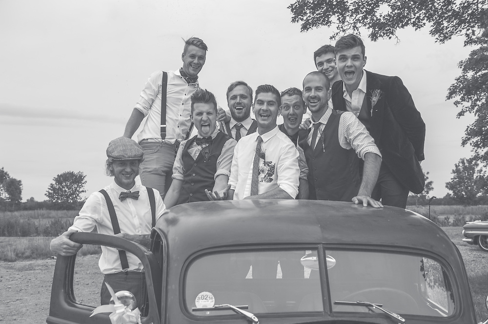A group shot of all the groomsmen and friends at a country themed wedding.