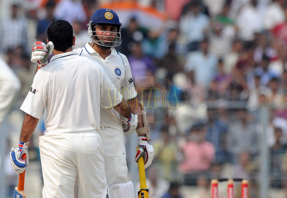 VVS Laxman of India congratulates teammate Mahendra Singh Dhoni captain of India  as he reaches his century during the 2nd day of the 2nd test match between India and The West Indies held at Eden gardens in Kolkata, India on the 15th November 2011..Photo by Pal Pillai/BCCI/SPORTZPICS