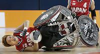 NLD-20040924-ATHENE: Paralympics 2004. ROLSTOELRUGBY: Belgie-Japan 36-35. De Japanner Manabu Tamura is omver gereden maar behoudt de bal, vrijdag tijdens de rolstoelrugbywedstrijd Belgie - Japan op de Paralympics 2004 in Athene. ANP FOTO/KOEN SUYK