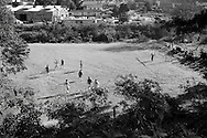 A youth football match taking place on a bare soccer pitch at Mbabane, Swaziland. The Kingdom of Swaziland (population 1.1m), a small, landlocked country in southern Africa was bordered by South Africa on three sides and Mozambique to the east, with Mbabane as its administrative capital. At the start of the 21st century, the country had the highest incidence per head of population of HIV/Aids in the world and and high levels of poverty mainly in rural areas where 75 per cent of the population lived.