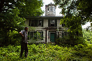 Roy Hunter of Claremont, N.H., stands  in front of his former home on July 8, 2014. Hunter had been evicted for unpaid taxes but was allowed on the property to remove possessions. (Valley News - Will Parson)