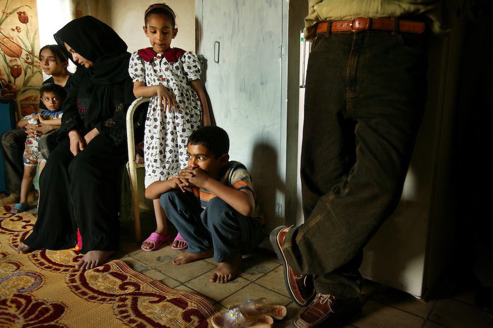 """A family from Fallujah rests inside a home, Baghdad, Iraq, April 12, 2005. They escaped by crawling on their knees to an ambulance and then traveling to Baghdad in a refrigerated meat truck. Intesar Jamil, in black, said, """"Every time we tried to leave the house to get food, the Americans would shoot at us.""""  Hospital officials in Fallujah report more than 600 killed and more than 1200 wounded, most of which they say were women, children and elderly."""