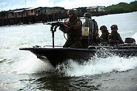 Members of the Colombian Navy patrol the waters along the coast that are used to ship drugs in Buenaventura, on the Pacific Coast of Colombia, on Monday, May 14, 2007. Buenaventura is in the midst of a spree of violence over control of drug shipments from the poor barrios in the city. Many of the neighborhoods have a strong presence of FARC militias that control most of the drug trade in the city. (Photo/Scott Dalton)