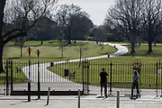 As the second week of the UK government's Coronavirus lockdown ends on a fine Spring weekend, and 24hrs after it was reported that 3,000 Londoners had been counted in Brockwell Park, Herne Hill, resulting in the closure of this significant public green space by Lambeth council, the piblic stand at the closed gates (See a similar view with many people 2 days before in Getty image #1209106121), on 5th April 2020, in London, England.