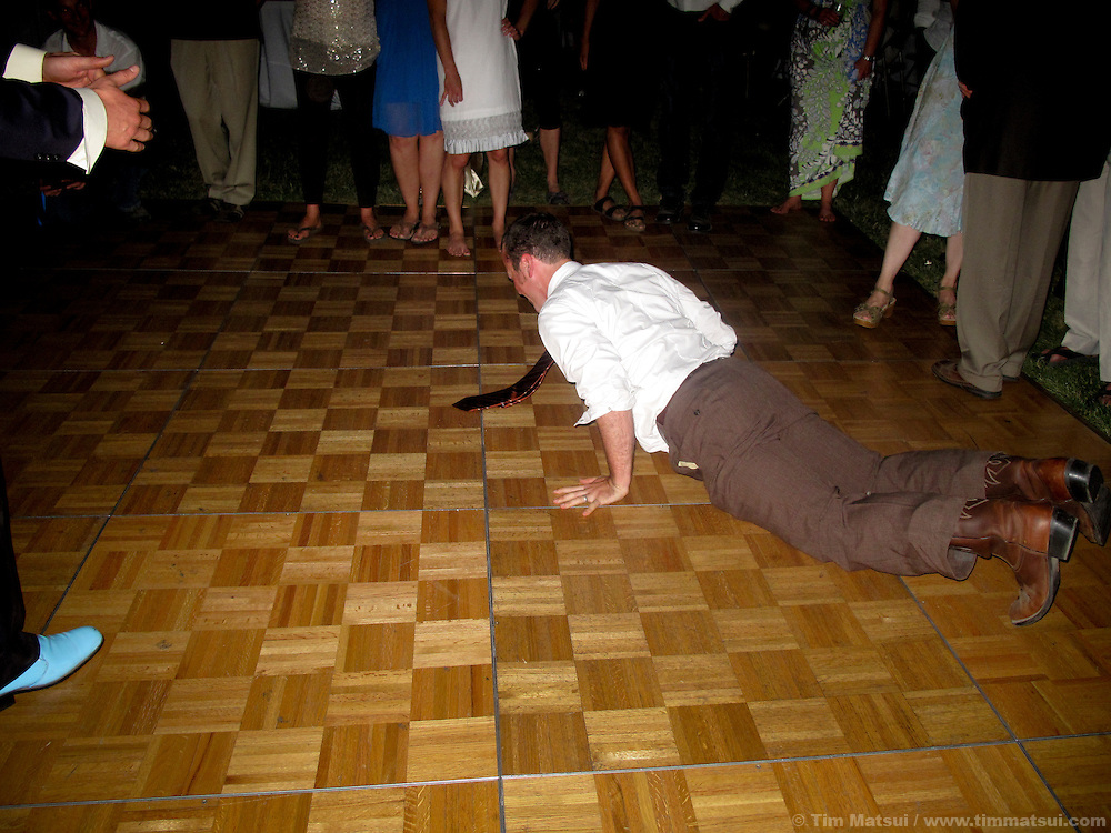 A caucasian man breakdances humorously on a dance floor doing the worm while at a party at night.