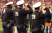 Three Cincinnati policemen salute during the playing of the National Anthem while wearing the number of Cincinnati Bengals defensive tackle Devon Still (75) in support of his daughter Leah Still who is fighting cancer while attending her first NFL game during the Cincinnati Bengals NFL week 10 regular season football game against the Cleveland Browns on Thursday, Nov. 6, 2014 in Cincinnati. The Browns won the game 24-3. ©Paul Anthony Spinelli