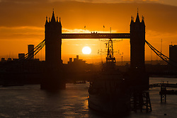© Licensed to London News Pictures. 24/02/2017. LONDON, UK.  A golden sunrise behind Tower Bridge in London this morning. Calm and sunny weather is forecast for London and the south east today, now that Storm Doris has passed. Photo credit: Vickie Flores/LNP