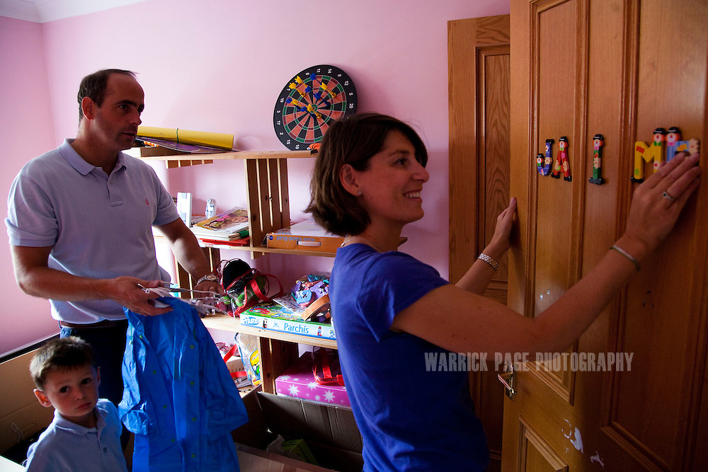 Eva Vildosola puts the name of her son Jamie on his bedroom door as she unpacks the remainder her family's belongings with her husband Julio and son Pablo, in their new home, on September 1, 2012, in Buckden, England. The Spanish family immigrated to England due to the ongoing economic crisis that has impacted heavily on Spain. (Photo by Warrick Page)