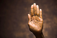 A black african hand holding a penny.