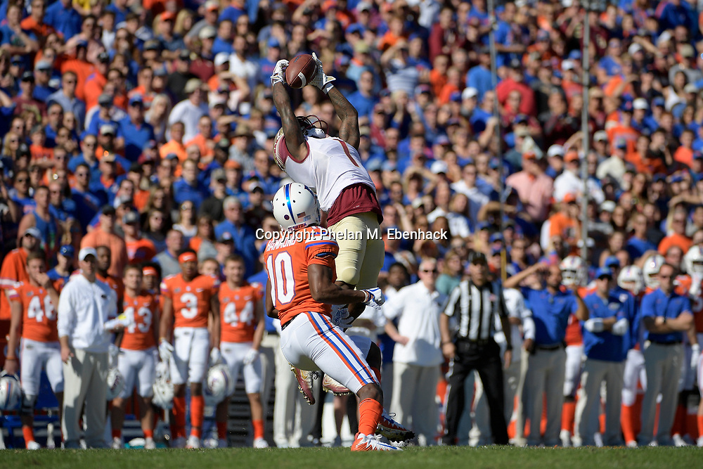 Florida State defensive back Levonta Taylor (1) intercepts a pass intended for Florida wide receiver Josh Hammond (10) during the first half of an NCAA college football game Saturday, Nov. 25, 2017, in Gainesville, Fla. (Photo by Phelan M. Ebenhack)