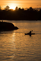 Paddlers cruise towards the sunset in the Harbour of Victoria, BC as a frieghter is seen in the far distance.